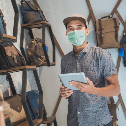 Mitarbeiter steht mit Maske im Laden vor Rucksaecken mit Tablet in der Hand fulfillmenttools