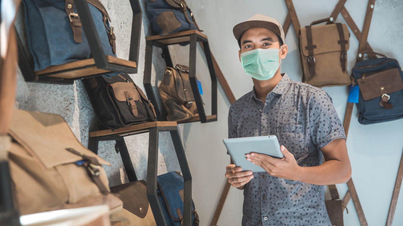 Mann mit Maske im Ladengeschaeft